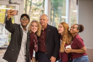 Chancellor Carlo Montemagno takes a selfie with several students