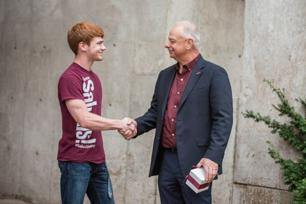 Chancellor Carlo Montemagno shakes hands with Logan Jerolds