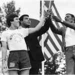 Three men hold up Flame of Hope